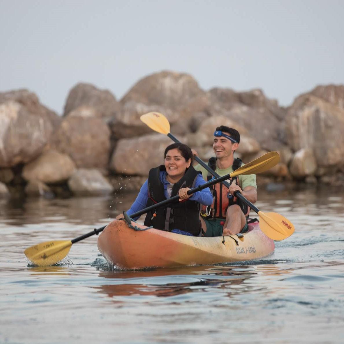 Two folx paddling a kayak